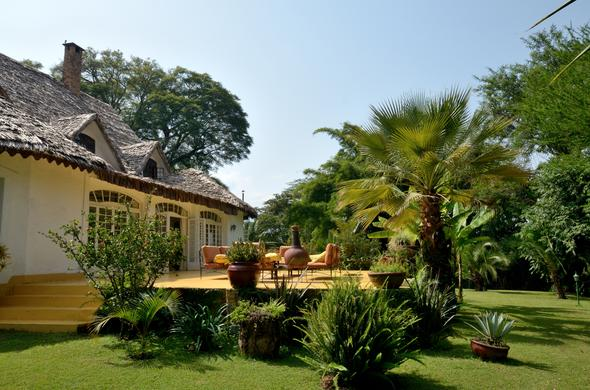 The patio is located among the lush greens of the garden at Arusha Safari Lodge.