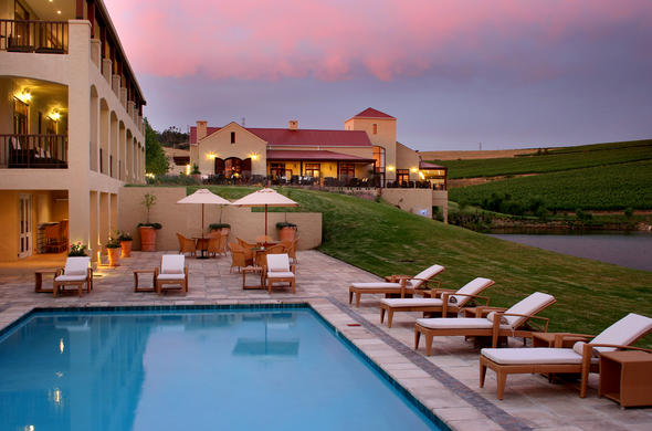 Exterior of Asara Hotel and pool at dusk.