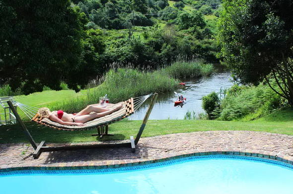 Guest relaxing poolside at Blackwaters River Lodge.