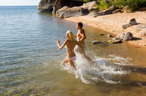Couple on holiday in Malawi running on the lakeshore..