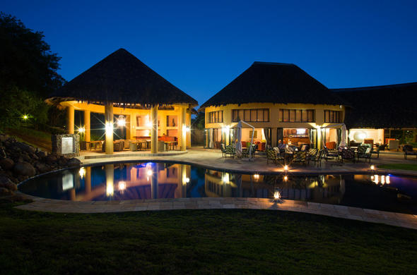 Ivory Tree Game Lodge swimming pool and deck area at night.