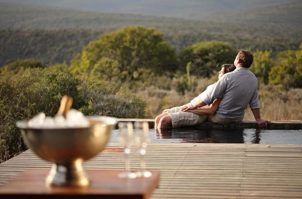 Kwandwe Game Reserve couple relaxing on safari on the pool deck.