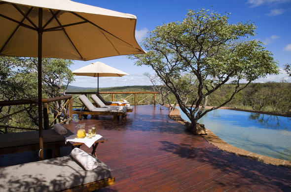 Relax with a drink on the scenic Nungubane Game Lodge pool deck.
