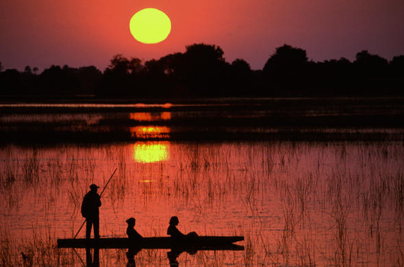 Mokoro ride on the Okavango Delta waterways at sunset.