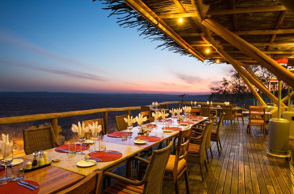 Gather around the table for dinner on the deck of Ongava Tented Camp.