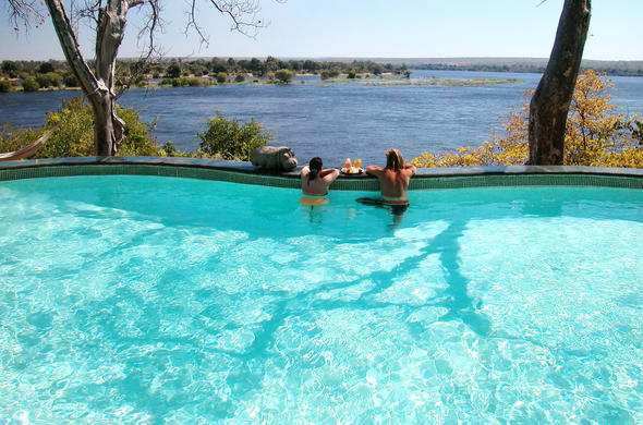 Guests enjoy scenic Zambezi River views from the pool of the River Club.