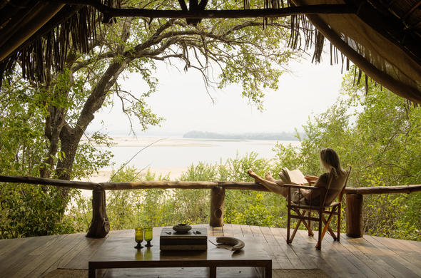 Relax with a book on the private deck of Sand Rivers Selous.