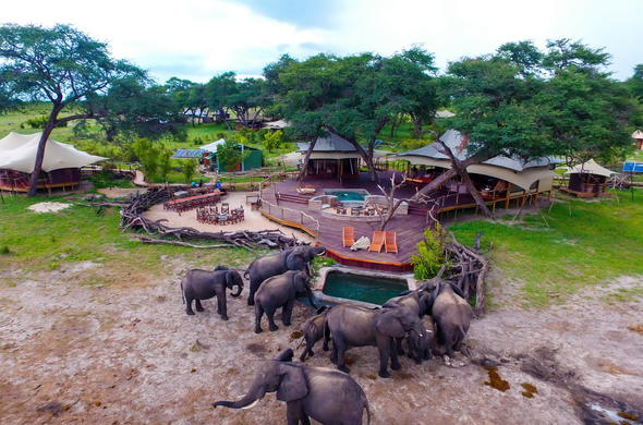 Aerial view of lodge with elephants cooling down at pool.