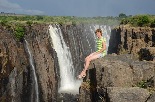 Woman sitting on the edge of Victoria Falls.